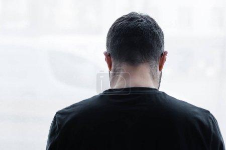 Photo pour Vue arrière de l'homme court solitaire de cheveux restant par la fenêtre à la maison - image libre de droit