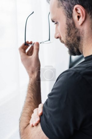 Photo for Sad bearded man holding glasses while standing by window and looking down - Royalty Free Image