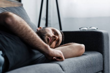 Photo for Depressed man lying on grey sofa at home and looking away - Royalty Free Image