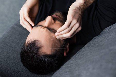 Photo pour Vue aérienne de l'homme se trouvant avec les yeux fermés et se tenant des mains près de la tête - image libre de droit