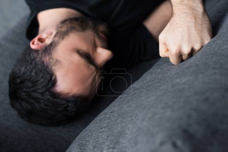 Photo for Overhead view of depressed man lying on sofa and kicking it with fist - Royalty Free Image