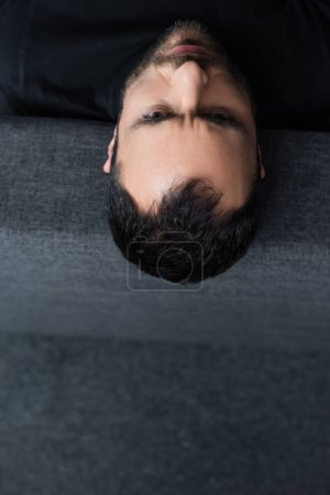 Photo for Overhead view of short haired depressed man lying on grey sofa at home - Royalty Free Image