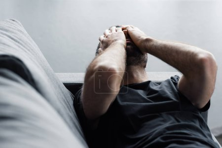 Photo for Depressed man lying on sofa and suffering while holding hands on face - Royalty Free Image