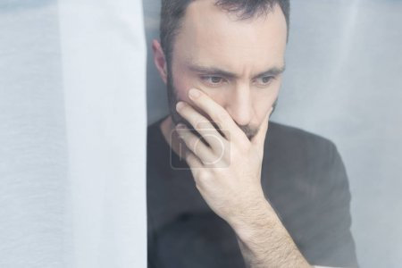 Photo pour Bel homme en t-shirt noir debout par la fenêtre et la main de fixation sur la bouche - image libre de droit
