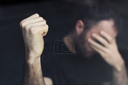 selective focus of depressed man with hand on face holding hand in fist