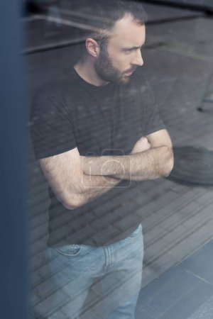 Photo for Handsome serious man with crossed arms standing by window and looking away - Royalty Free Image