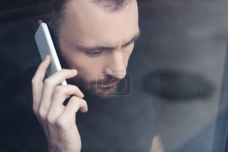 Photo for Upset handsome man standing by window with smartphone and looking away - Royalty Free Image