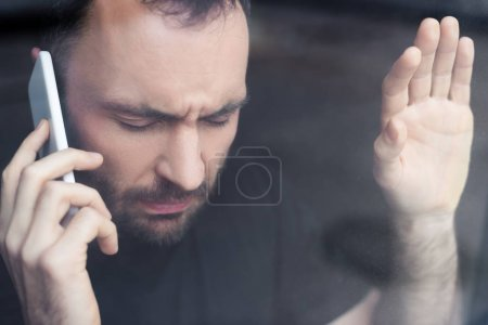 Photo for Stressed man with closed eyes holding smartphone while standing by window - Royalty Free Image
