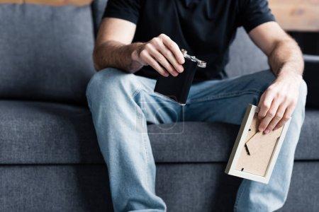 Foto de Vista parcial del hombre sentado en el sofá gris y sosteniendo marco de la foto y matraz con alcohol - Imagen libre de derechos
