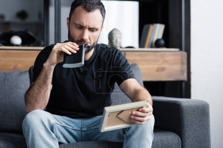 Foto de Depressed man drinking from flask and holding photo frame while sitting on sofa at home - Imagen libre de derechos