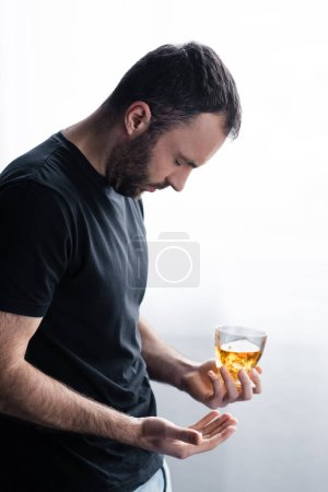 Photo for Depressed bearded man standing with closed eyes and holding glass of whiskey - Royalty Free Image