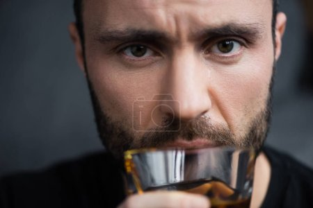 Photo for Selective focus of depressed man holding glass of whiskey and looking at camera - Royalty Free Image