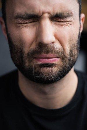 Photo pour Portrait de bel homme non rasé déprimé pleurant avec les yeux fermés - image libre de droit