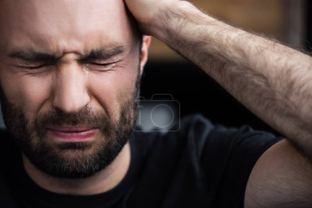 Photo for Depressed bearded man crying with closed eyes and holding hand on head - Royalty Free Image