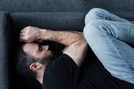Photo pour Vue supérieure de l'homme barbu déprimé souffrant tout en se trouvant sur le sofa avec les yeux fermés - image libre de droit