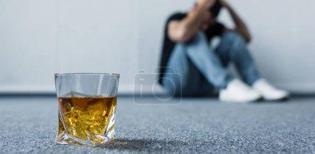 Photo pour Foyer sélectif de l'homme déprimé assis sur le sol par mur près du verre de whisky - image libre de droit