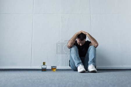 Photo for Depressed man sitting on floor by white wall near bottle and glass of whiskey - Royalty Free Image