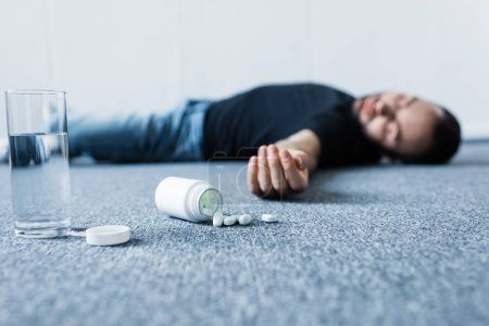 Photo for Selective focus of unconscious man lying on grey floor near glass of water and container with pills - Royalty Free Image
