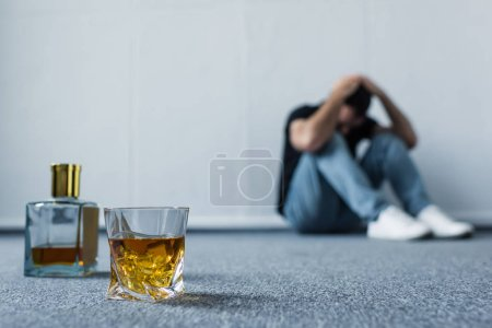Photo for Selective focus of suffering man sitting on floor by white wall near bottle and glass with whiskey - Royalty Free Image
