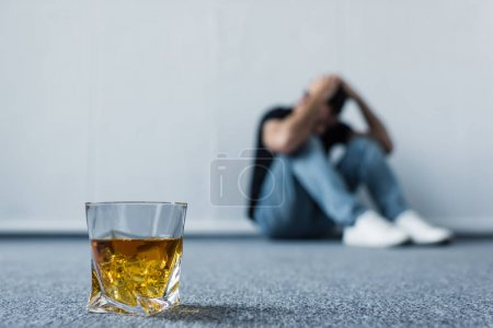 Photo for Selective focus of depressed man sitting on floor by white wall near glass of whiskey - Royalty Free Image