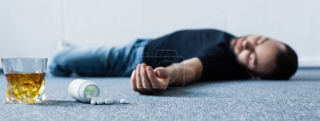 Photo for Panoramic shot of unconscious man lying on grey floor near glass of whiskey and container with pills - Royalty Free Image