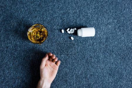 Photo for Top view of male hand near container with pills near glass of whiskey and container with pills - Royalty Free Image