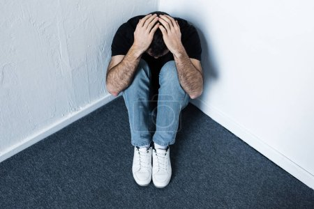 Photo for Depressed man sitting on grey floor in corner and holding hands on head - Royalty Free Image