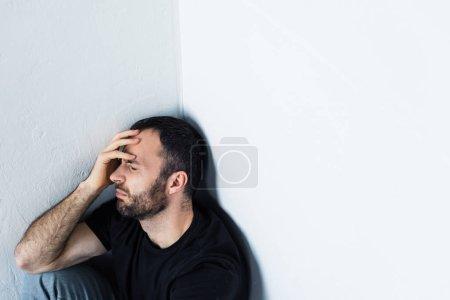 Photo for Depressed man sitting in corner with closed eyes and holding hand on forehead - Royalty Free Image