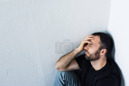 Photo for High angle view of upset man sitting in corner with closed eyes and holding hand on forehead - Royalty Free Image