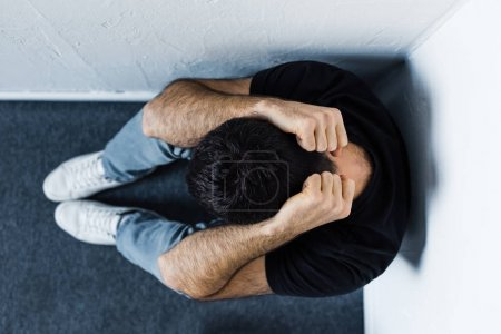 Photo for Top view of adult depressed man sitting on floor in corner and holding hands on head - Royalty Free Image