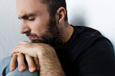 Photo for Adult depressed man suffering while sitting by white wall with closed eyes - Royalty Free Image