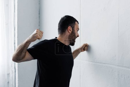 Photo for Angry bearded man in black t-shirt screaming and kicking white wall - Royalty Free Image