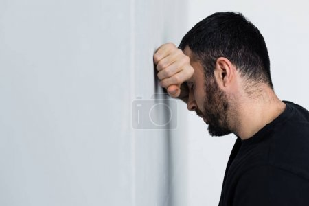 Photo for Depressed unshaven man standing near white wall with closed eyes - Royalty Free Image