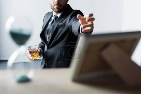 Photo for Selective focus of man in suit holding glass of whiskey and outstretching hand to table with hourglass and photo frame - Royalty Free Image