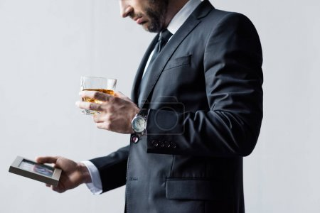 Photo pour Vue partielle de l'homme dans le verre de fixation de procès de whiskey et de photo dans le cadre - image libre de droit