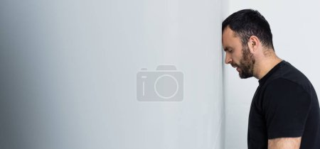 Photo for Panoramic shot of depressed bearded man standing by white wall with closed eyes - Royalty Free Image