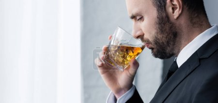 Photo for Panoramic shot of sad, handsome bearded man drinking whiskey - Royalty Free Image