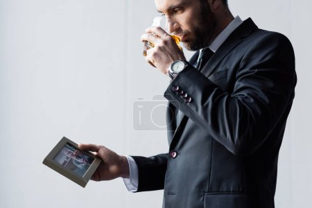 Photo for Upset man in suit drinking whiskey and looking at photo in frame - Royalty Free Image