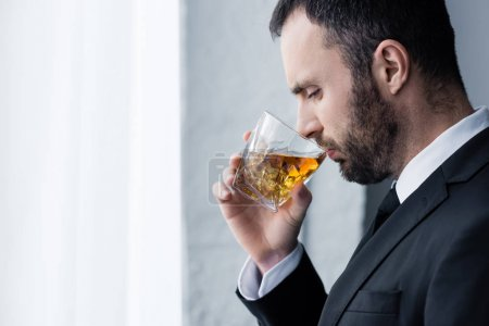Photo for Side view of frustrated, handsome bearded man drinking whiskey - Royalty Free Image