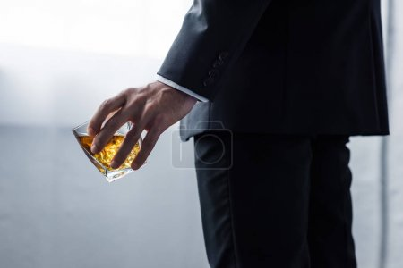 Photo for Partial view of man in black suit holding glass of whiskey - Royalty Free Image