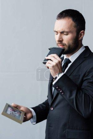 Photo pour Homme beau bouleversé buvant de flacon avec les yeux fermés tout en retenant la photo dans le cadre - image libre de droit