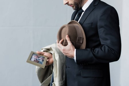 Photo for Partial view of man in suit holding hat in hand while looking at photo in frame - Royalty Free Image