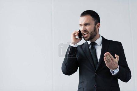 Photo pour Homme d'affaires en colère en costume noir querelle tout en parlant sur smartphone - image libre de droit