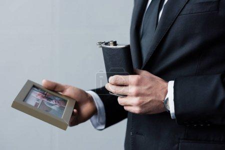 Photo pour Vue recadrée de l'homme en costume tenant fiole et photo dans le cadre - image libre de droit