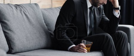 Photo for Panoramic shot of depressed man sitting on sofa with glass of whiskey - Royalty Free Image