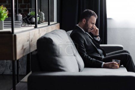 Photo for Sad businessman in suit sitting on sofa with smartphone and glass of whiskey - Royalty Free Image