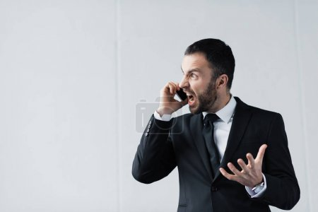 Photo for Angry businessman in black suit quarreling while talking on smartphone - Royalty Free Image