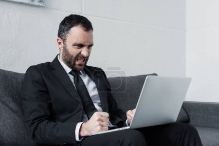 Photo for Angry businessman with hands in fists using laptop while sitting on sofa in office - Royalty Free Image