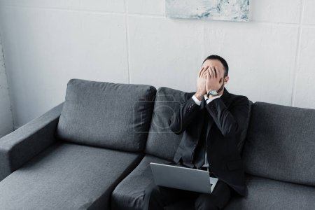 Photo for High angle view of upset businessman covering face with hands while sitting on sofa with laptop - Royalty Free Image