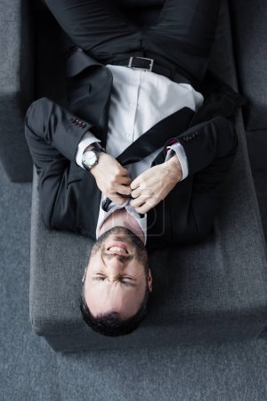 Photo for Top view of depressed businessman untying tie while lying on sofa - Royalty Free Image